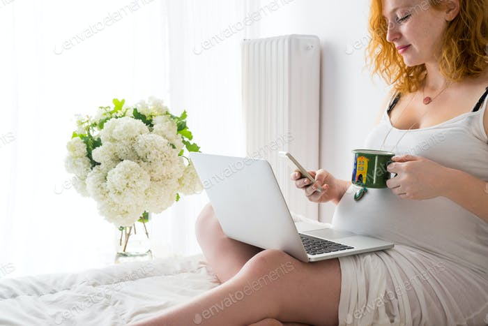 Happy pregnant woman relaxing on bed with a laptop, smartphone a