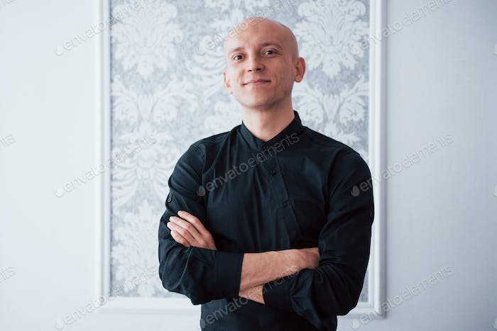 Portrait of cheerful guy in the classic black shirt with arms crossed