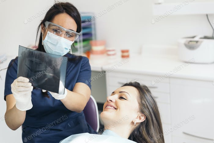 Doctor hablando con su paciente y enseñando una radiografía.
