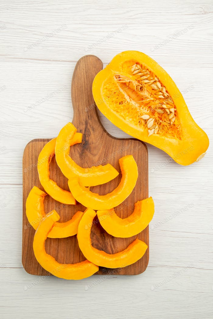 top view chopped butternut squash on cutting board half squash on grey table