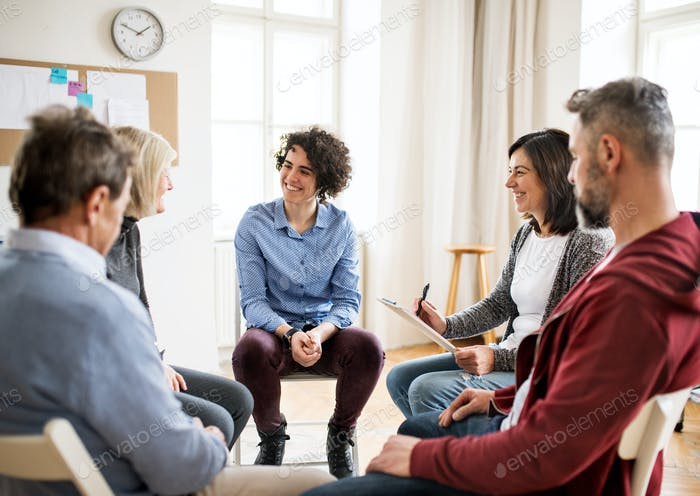 Men and women sitting in a circle during group therapy, talking.
