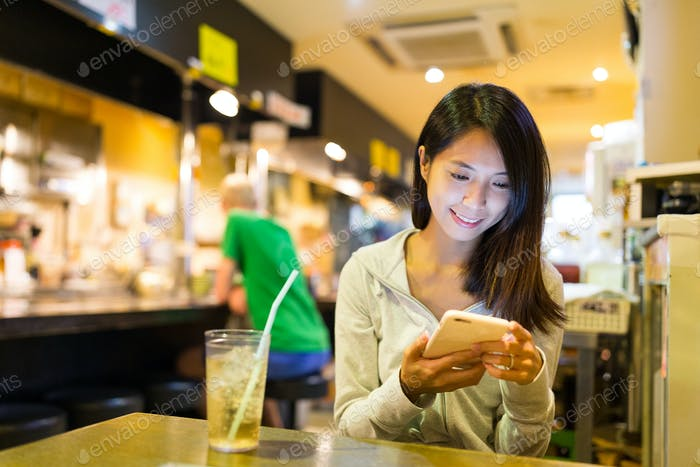 Woman checking on mobile phone in Japanese restaurant