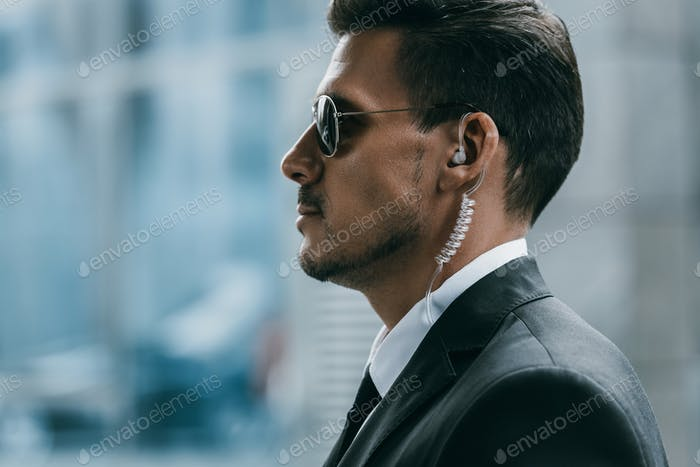 profile of handsome security guard with sunglasses and security earpiece