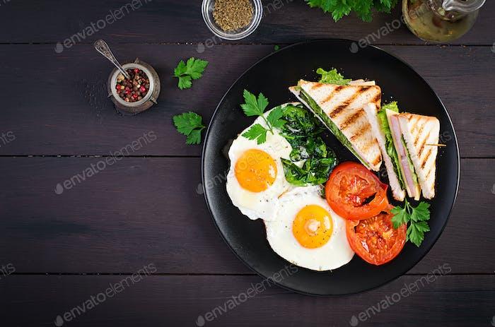 Frühstück: Spiegelei, Spinat, Tomaten und Club-Sandwich auf Teller. Draufsicht, Kopierbereich