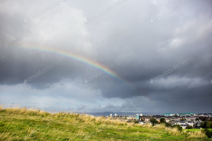 cloudy sky and rainbow above the city