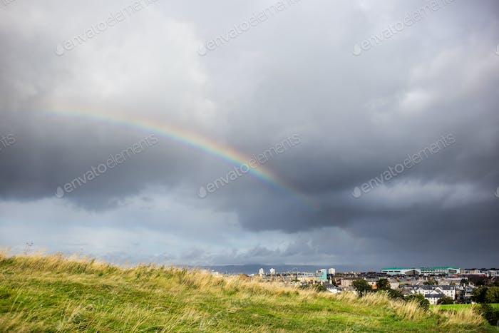 bewölkt Himmel und Regenbogen über der Stadt