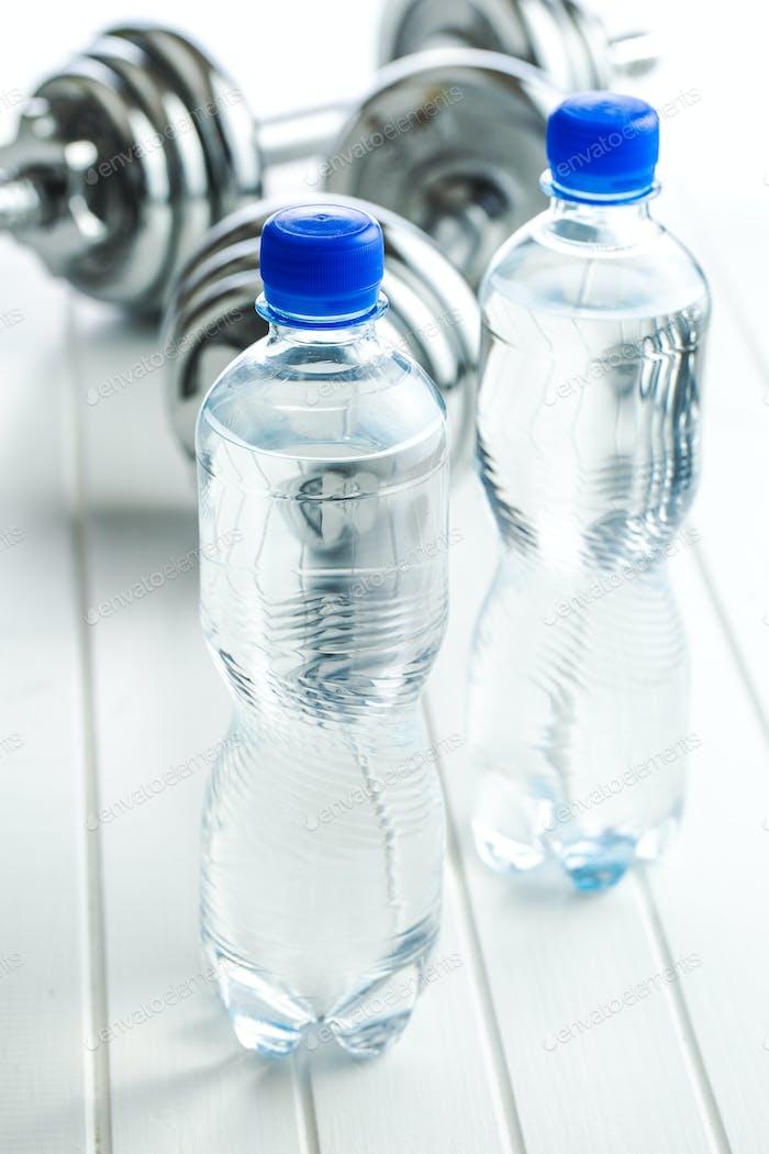 Flasche Wasser und Hantel.