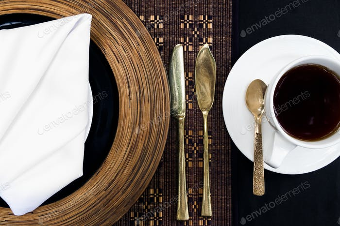 Golden silverware laid on a table with a plate and a cup