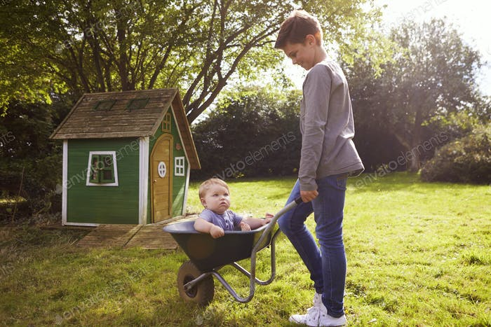 Junge schieben Baby Bruder In Garten Schubkarre