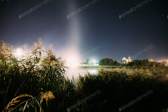 Evaporation Over River Lake Near Houses In Village. Night Starry Sky Above Misty Lake River