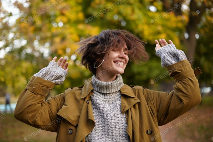 Pleased good looking young brown haired female waving her short hair and keeping hands raised