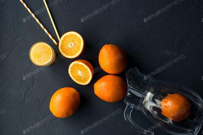Fresh orange juice and fresh fruit oranges on a black background