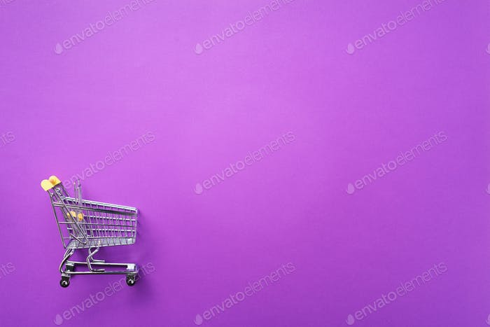 Shopping cart on violet background. Minimalism style. Creative design. Top view with copy space