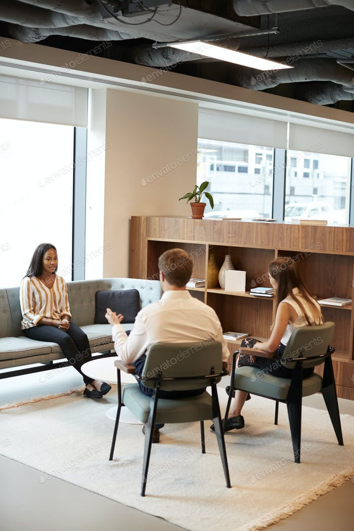 Businessman And Businesswoman Interviewing Female Candidate In Office