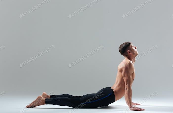 Fitness man doing yoga exercise