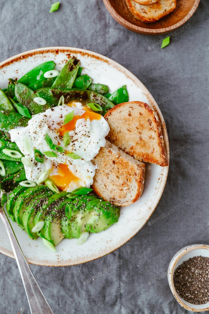 Fried snow peas, avocado, poached eggs are sprinkled chia seeds with toasts