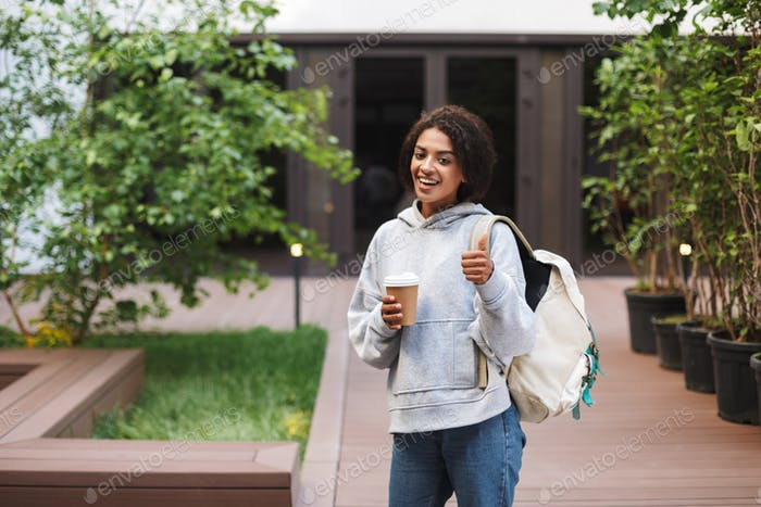 Smiling lady with dark curly hair standing with backpack and cup of coffee to go