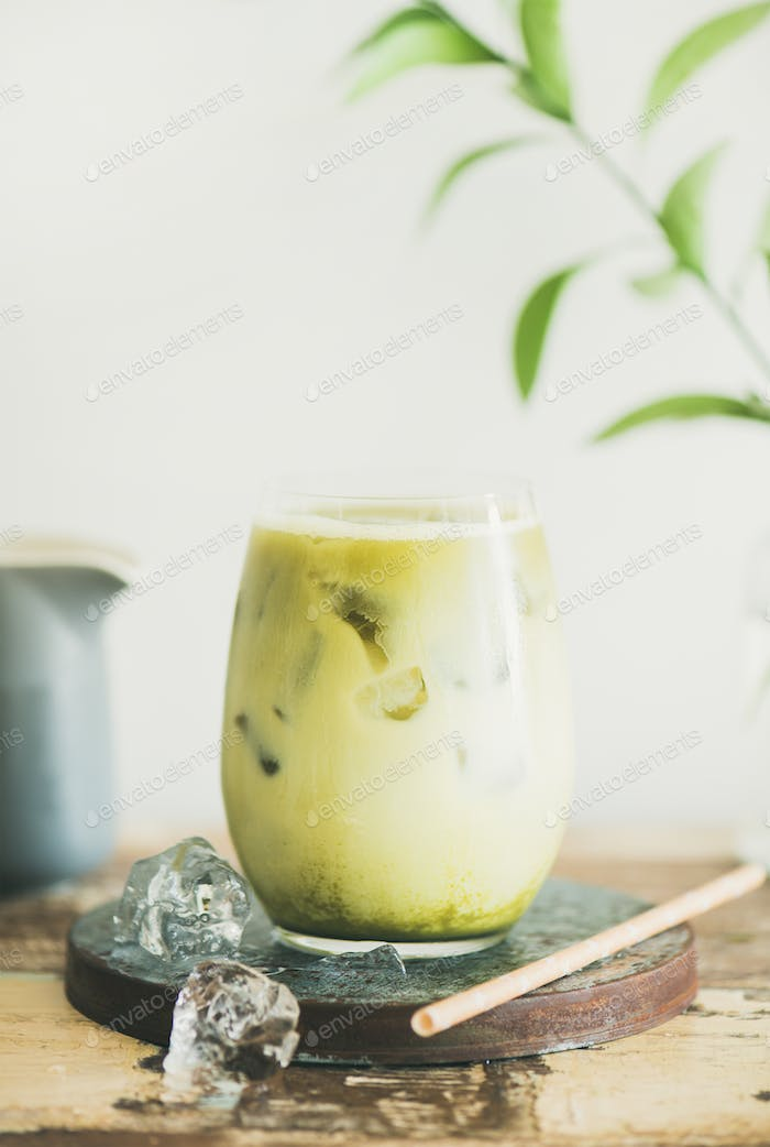 Iced matcha latte drink, white wall at background, close-up