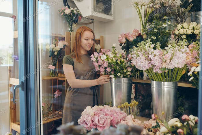 Young flower shop worker checking flowers