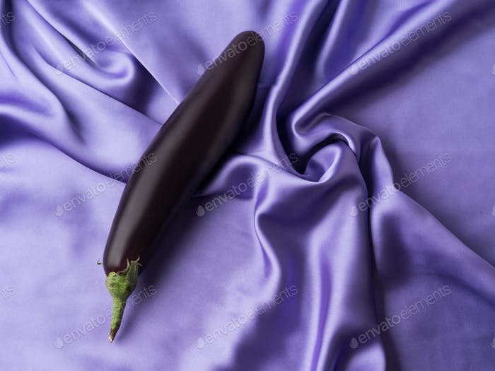Sex and orgasm concept with eggplant on crumpled silk sheet