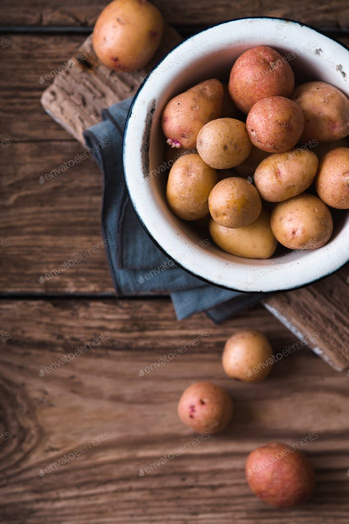 Raw potatoes in the metal bowl on the wooden table top view