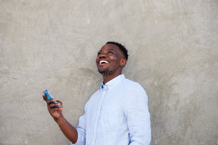 cheerful young african man with mobile phone standing by wall