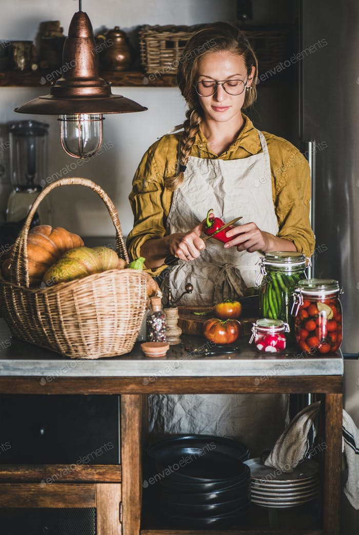 Young woman cooking vegetables preserves in kitchen
