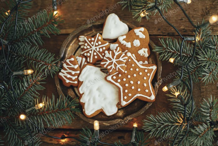 Christmas gingerbread cookies on plate, fir branches, lights on rustic wood, flat lay. Happy holiday