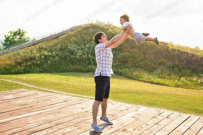 happy father holding little kid in arms, throwing baby in air. concept of happy family, fatherhood