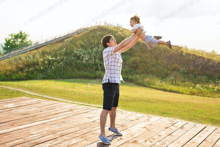 glücklicher Vater hält kleines Kind in den Armen, werfen Baby in der Luft. Konzept der glücklichen Familie, Vaterschaft