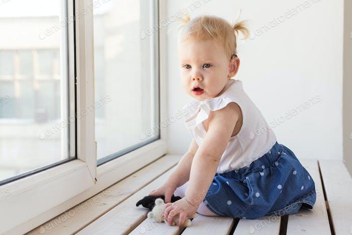 Baby trägt zu Hause ein Hörgerät. Behindertes Kind, Behinderung und Taubheit.