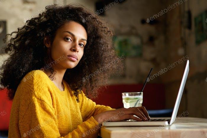 Ernste junge afrikanische Frau arbeitet auf Laptop in einem Café