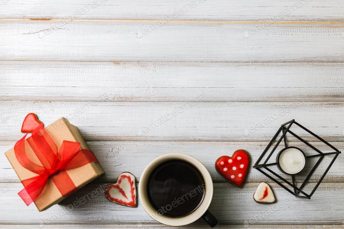 Box with a present to the Valentine's Day cookies in the shape of a heart and cups of black coffee