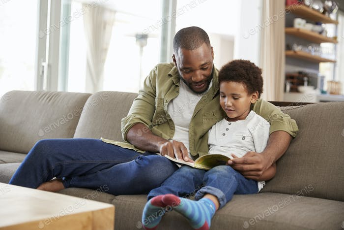 Father And Son Sitting On Sofa In Lounge Reading Book Together