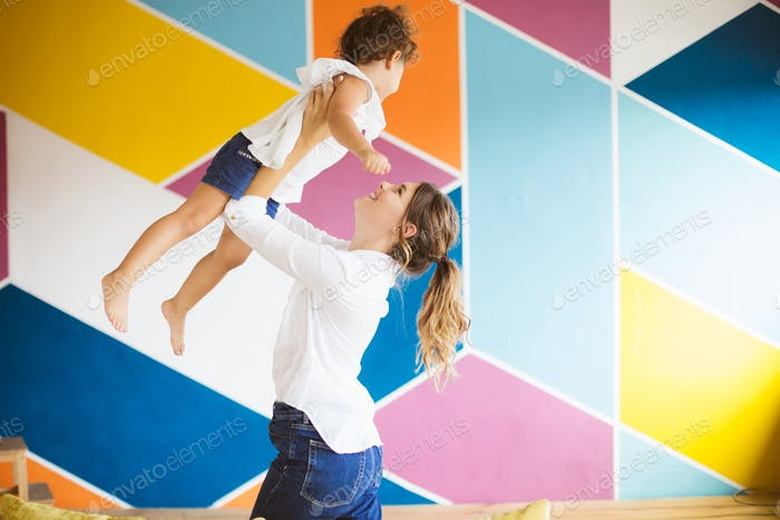 Young mother in white shirt joyfully lifting little pretty daugh