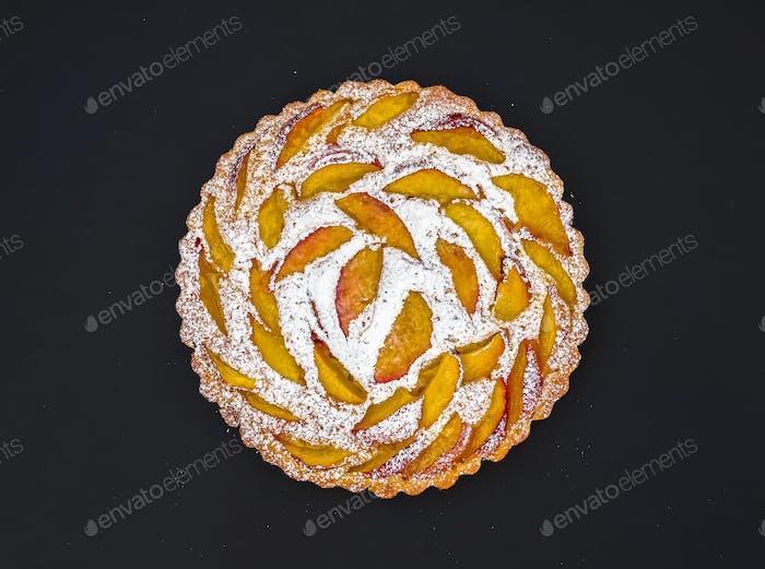 Peach pie with sugar powder on dark
