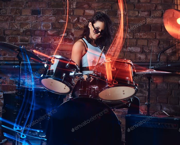 Beautiful girl musician in sunglasses holding the sticks sitting behind the drum set