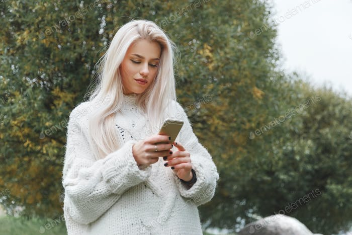Portrait of young caucasian blonde hair woman in white pullover uses the phone outdoor