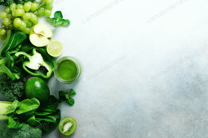 Green smoothie in glass jar with fresh organic green vegetables and fruits on grey background