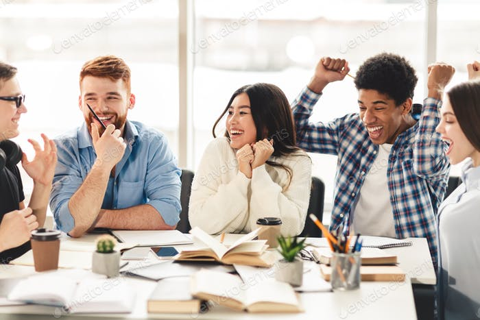 Friendship concept. Happy classmates talking in college library