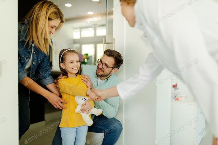 Eltern und Mädchen treffen sich mit dem Kieferorthopäden, der Zahnuntersuchung und der Zahnarztpraxis.
