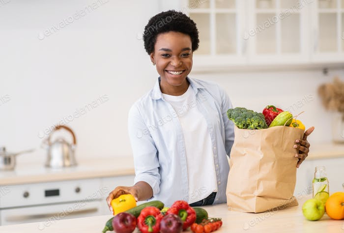 Black Woman Posing With Grocery Shopping Bag In Kitchen Indoor