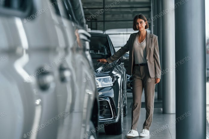 Woman is indoors near brand new automobile indoors