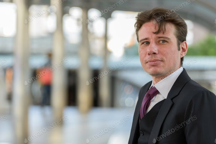 Portrait of businessman thinking outdoors in city