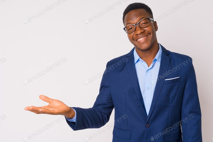 Portrait of young happy African businessman showing something