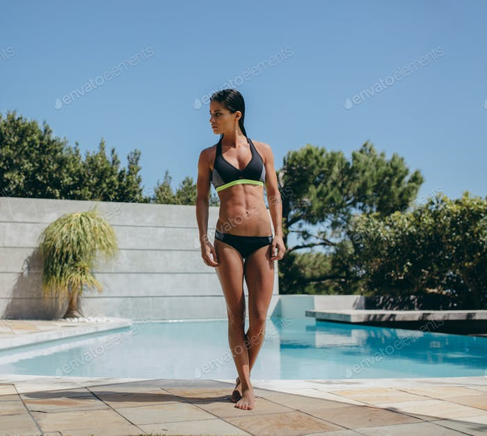 Female model walking out from the pool