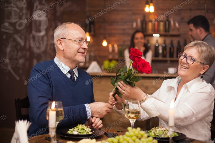 Schöne alte Dame bewundern die Blumen, die ihr Mann gab ihr
