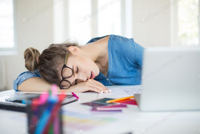 Young tired woman with eyeglasses on head sleeping on desk while