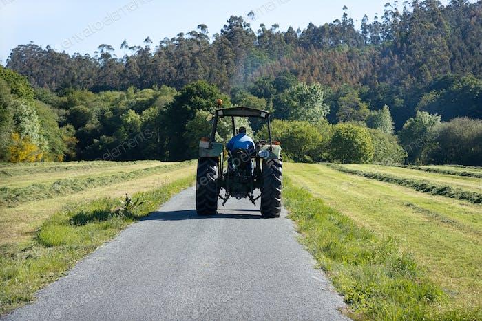 Szene eines alten Traktors auf einer Straße in einem ländlichen Gebiet