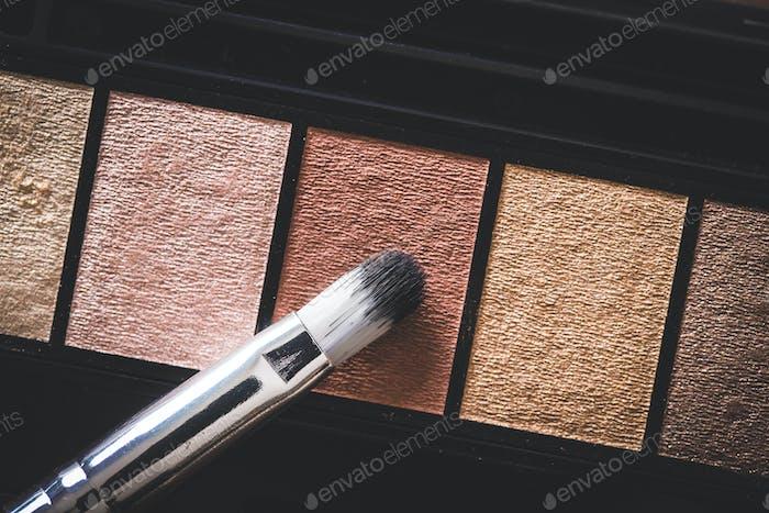 Eyeshadow powder and makeup brush.